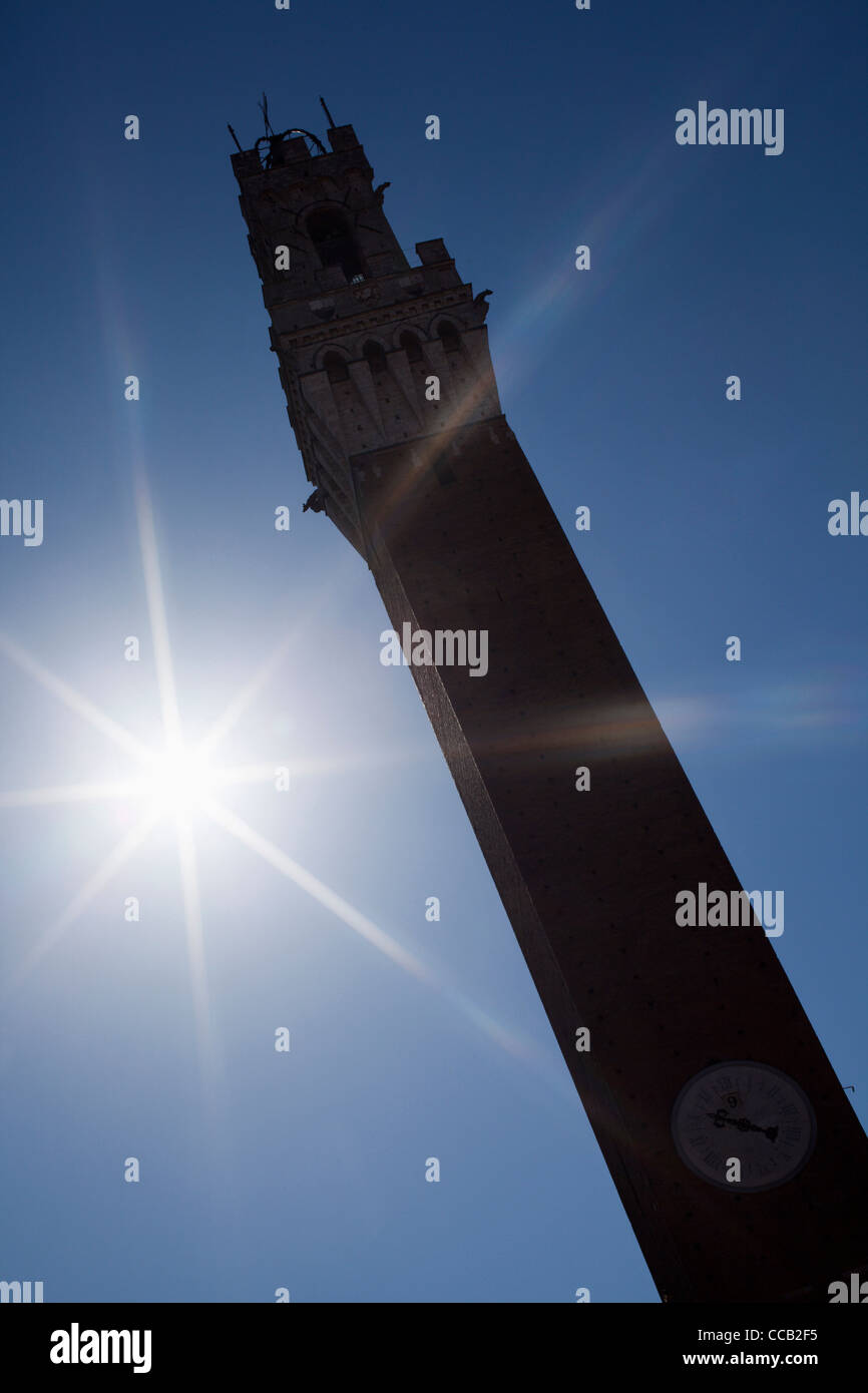 The sun beating down on the Torre del Mangia or tower of the Eater. Siena. Italy. - Stock Image