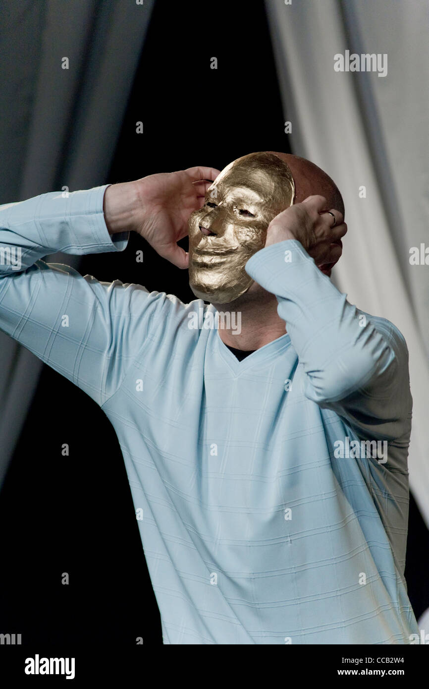 A Mime Artist on stage in a golden Mask - Stock Image