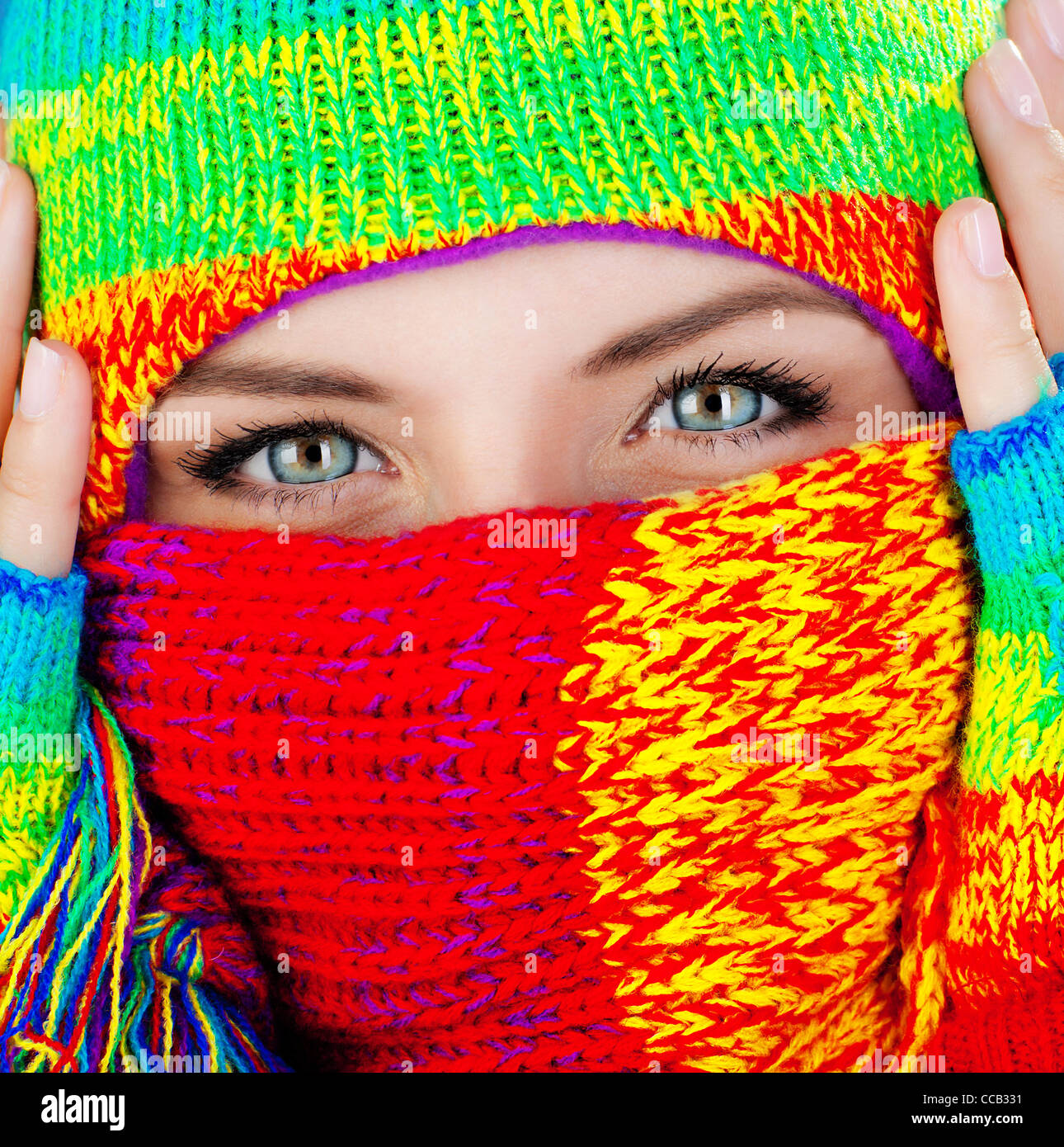 Close up portrait of a woman's covered face with beautiful blue eyes, female wearing colorful winter hat, girl - Stock Image