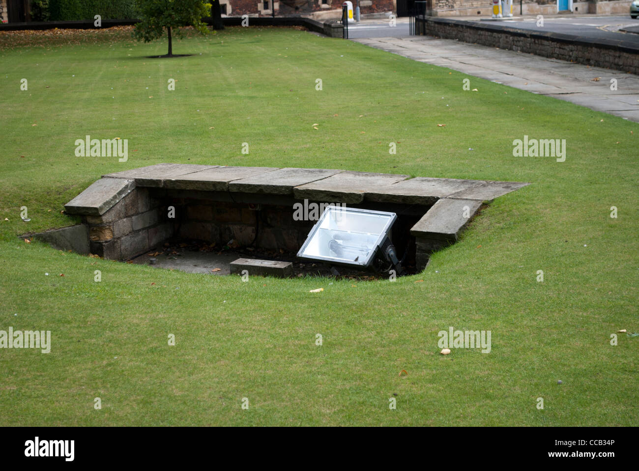 Spotlight behind low wall in the middle of a lawn by stone flagged path outside Lincoln Cathedral - Stock Image