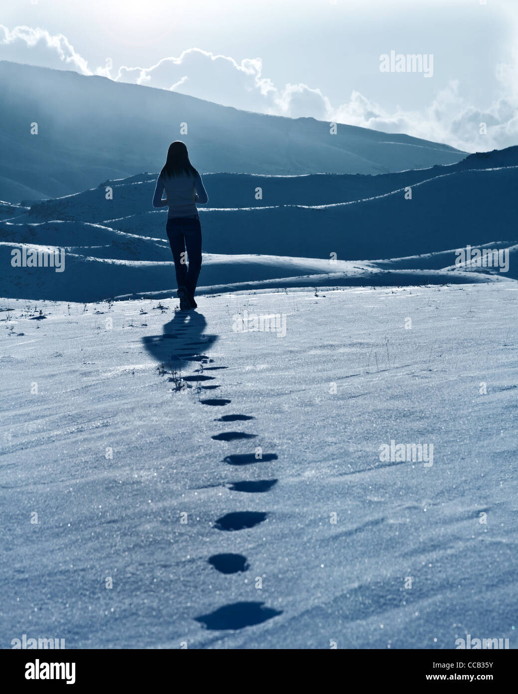 Lonely woman silhouette at winter mountains, footprints on the snow, enjoying wintertime nature view,one girl walking - Stock Image