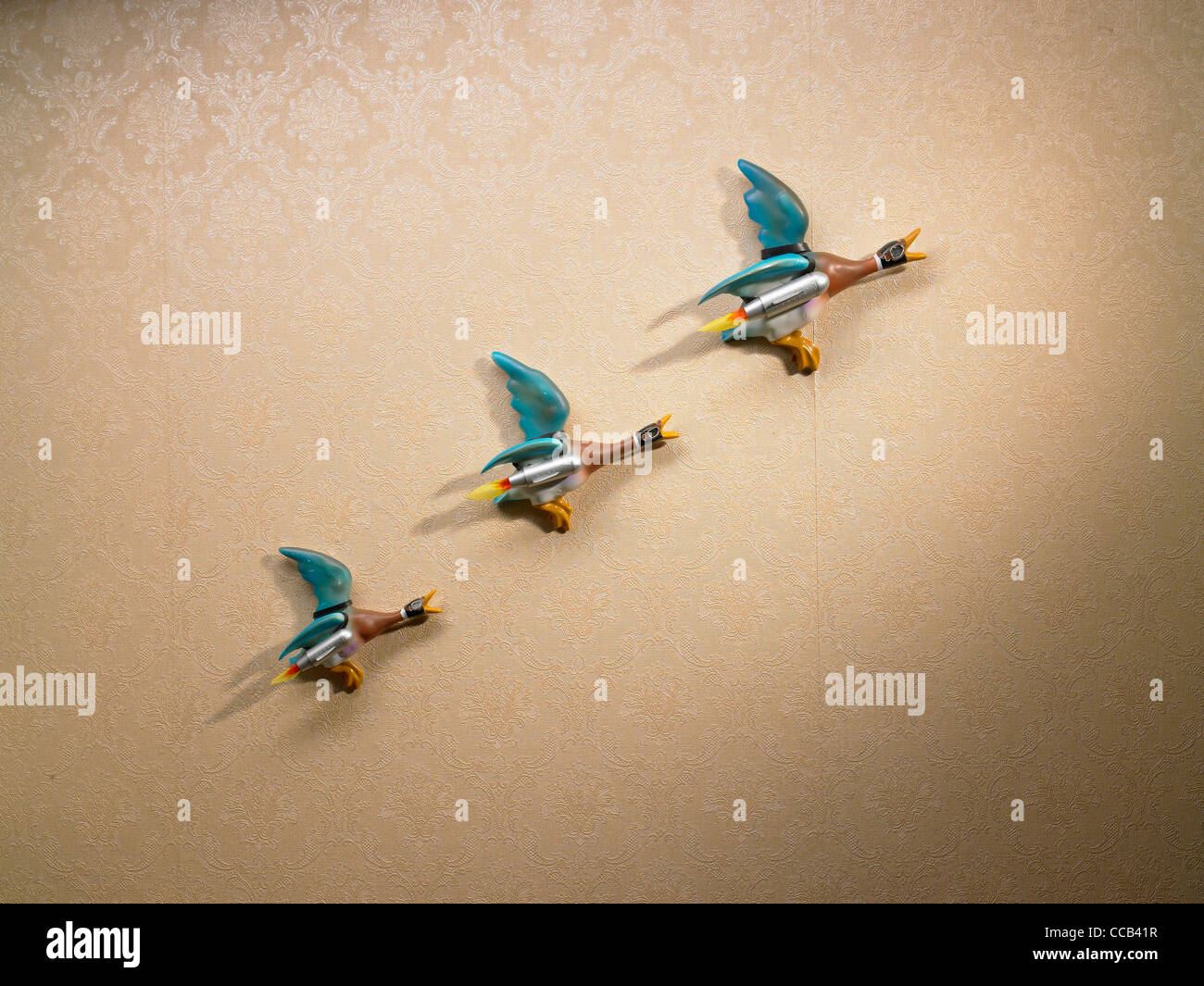 a line of rocket powered ducks on the wall - Stock Image