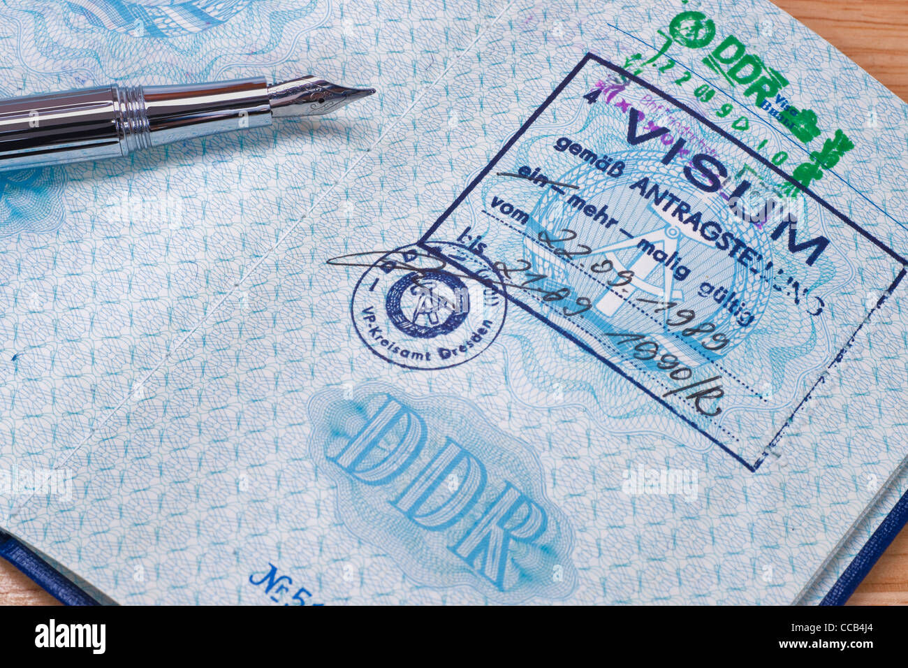 opened passport from GDR with a Visa and a stamp to border crossing at Friedrichstraße Berlin, a pen is alongside - Stock Image
