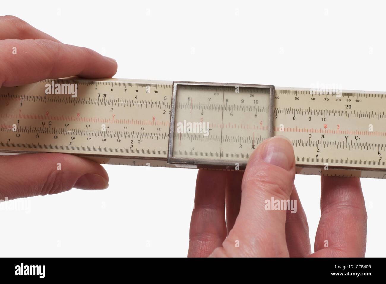 Ein Rechenschieber wird in der Hand gehalten | a slide rule is hand-held - Stock Image