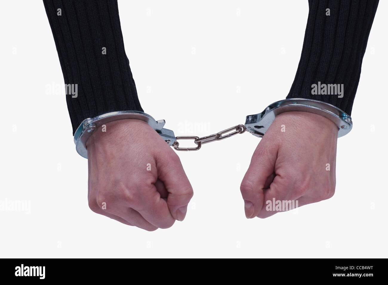 ein Mensch hat, durch Handschellen, gefesselte Hände   a man has hands tied up by handcuffs - Stock Image
