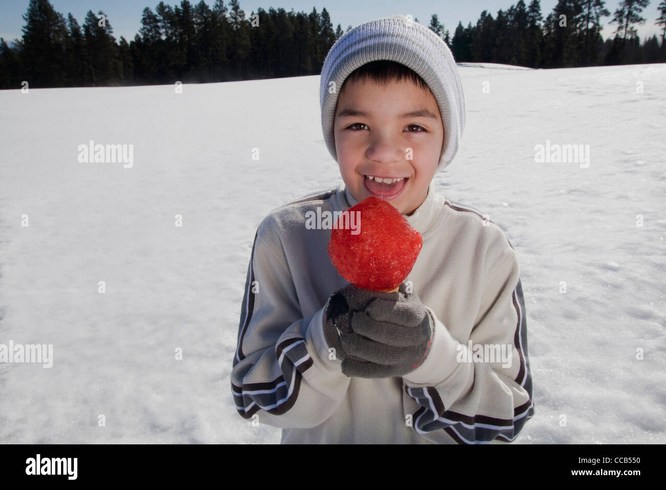 Boy 10 -12 yrs. old eating a snow cone outdoors on a winter day. - Stock Image