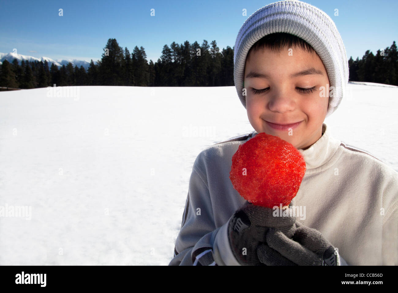 Boy 10 -12 yrs old eating a snow cone on a winter day outdoors. - Stock Image