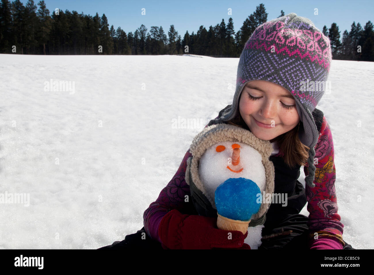 Girl making a snowman on a sunny winter day. - Stock Image