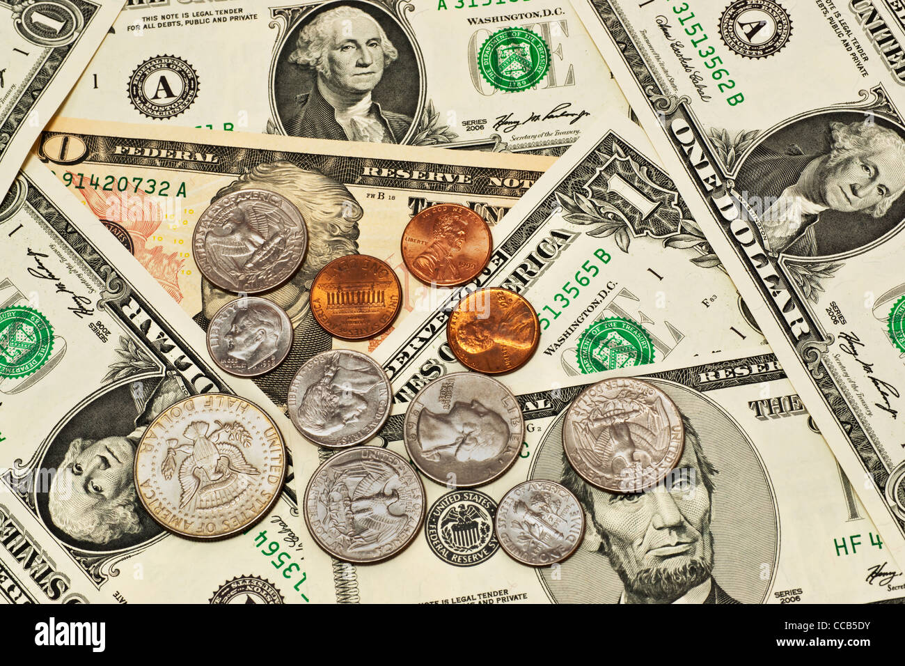 Detail photo of various U.S. American dollar bills, some coins are alongside - Stock Image