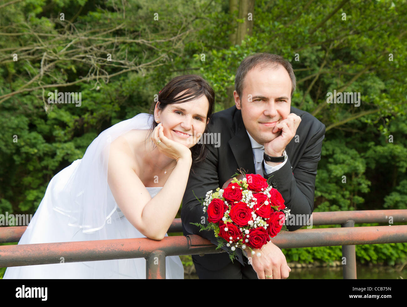newly wed couple with wedding gown, dark suit and rose bridal bouquet: groom and bride hand in hand proud and happy - Stock Image
