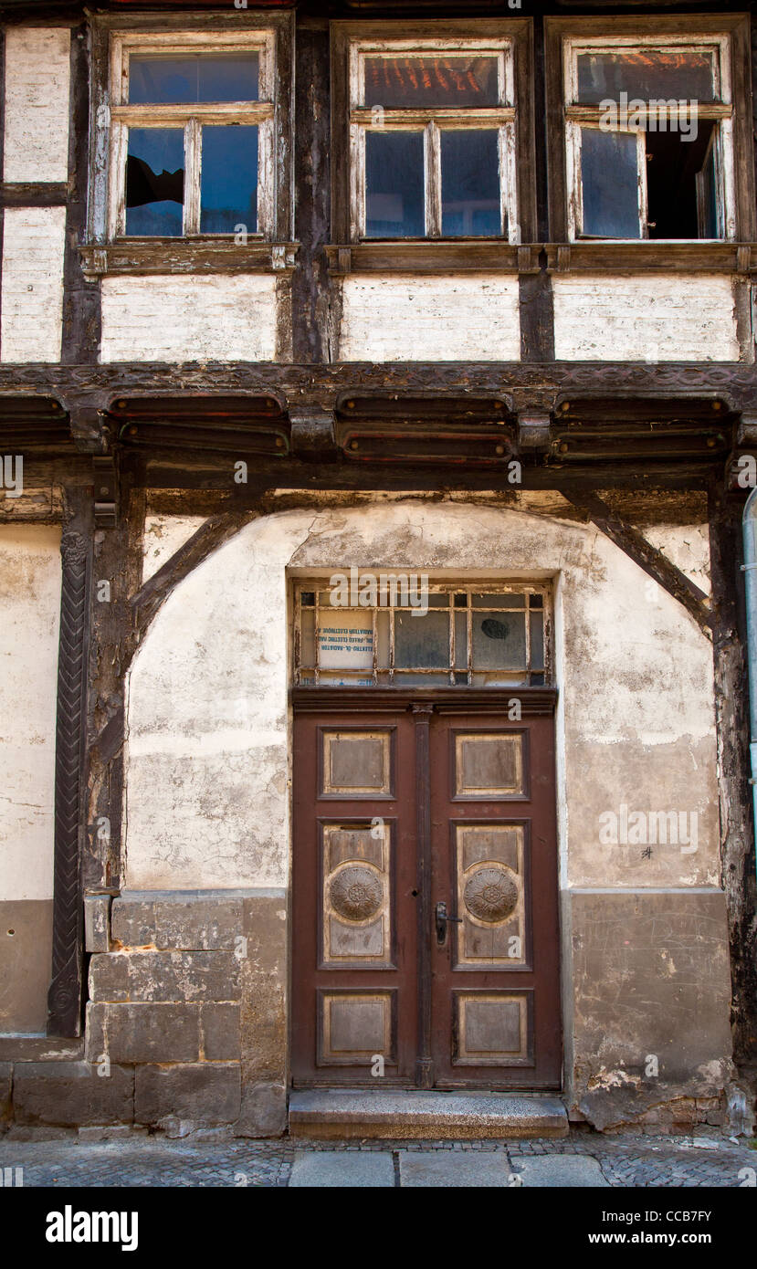 Old wooden front door and windows on a dilapidated timber framed house in UNESCO town of Quedlinburg in Saxony Anhalt, - Stock Image