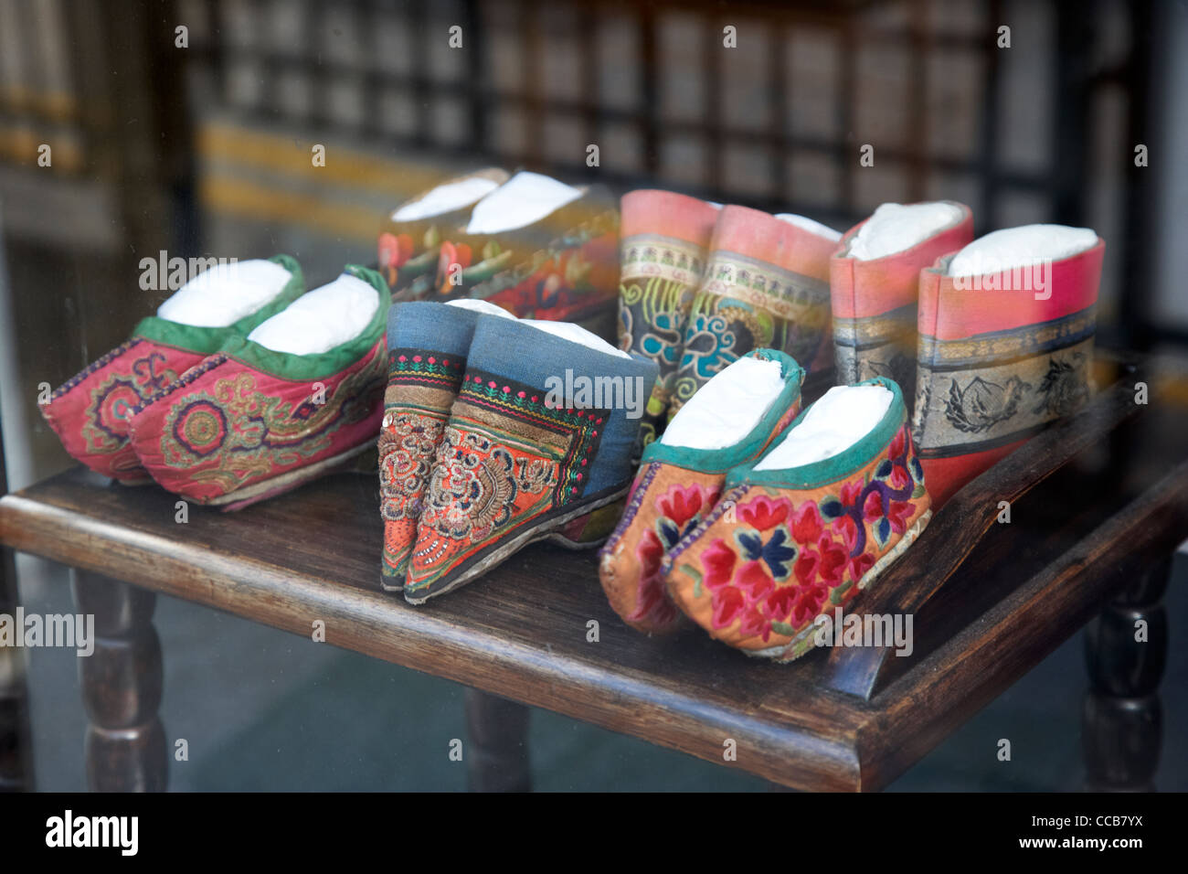 folk style traditional miniature embroidered slippers shoes in a shop window hong kong hksar china asia. - Stock Image