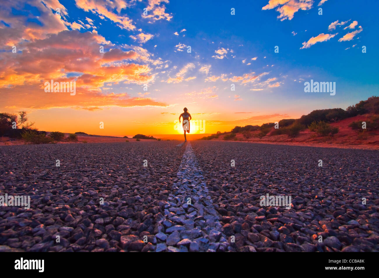 Female Runner jogging at Sunrise on a Remote Road in the Australian Outback, Monkey Mia, Western Australia, Australia - Stock Image