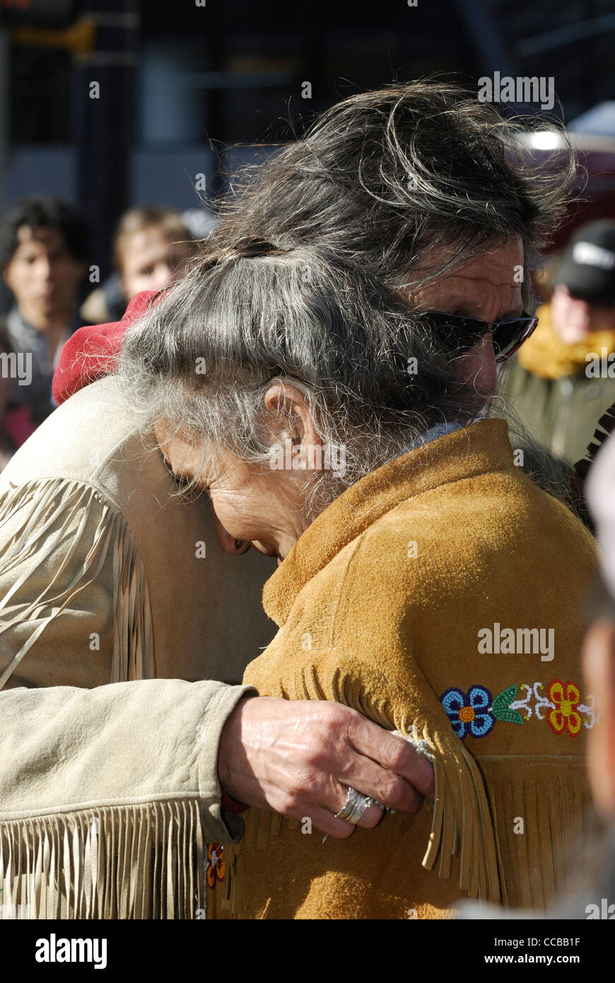 First Nations elders embracing each other. - Stock Image