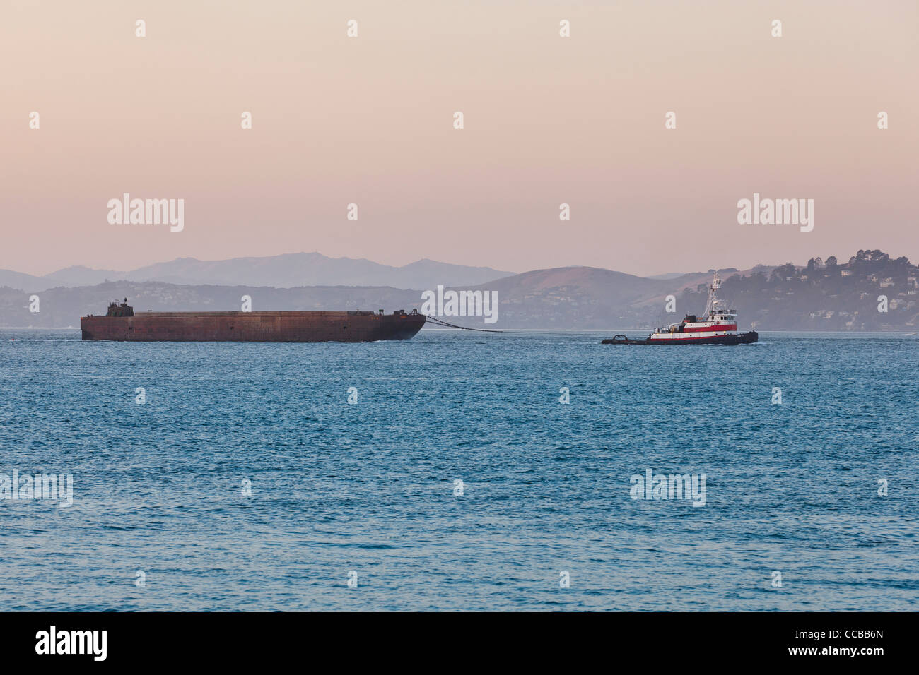 A barge being towed by tugboat - Stock Image