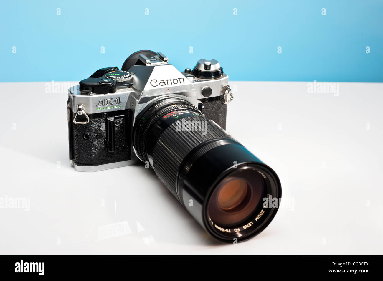 Canon AE-1 film camera with a long telephoto zoom lens attached. - Stock Image
