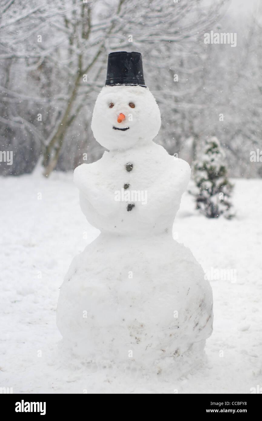 Happy snowman next to a christmas tree enjoying the falling snow - Stock Image