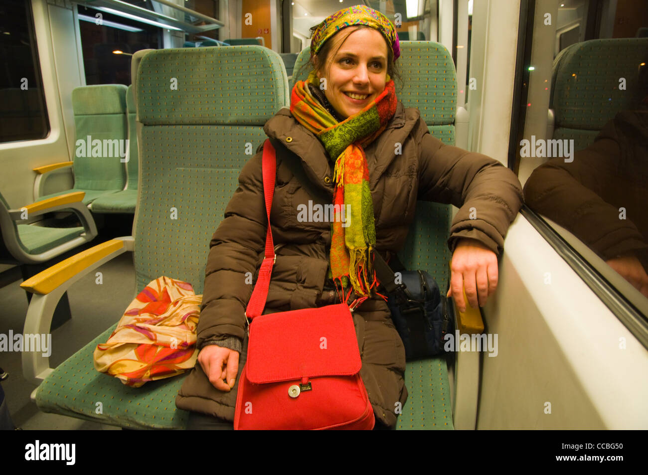 A woman in her late 20s travelling on narrow gauge train between Bavaria in Germany and Czech Republic Europe - Stock Image