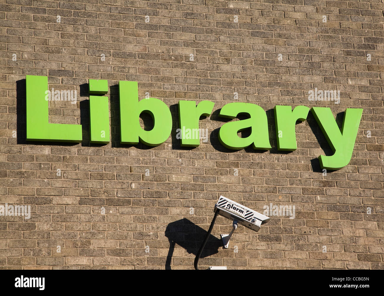 Library sign green letter brick wall CCTV camera - Stock Image