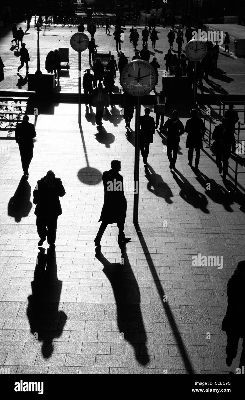 Shadows and silhouettes of pedestrians walking through Reuters Plaza, Canary Wharf, London, UK - Stock Image