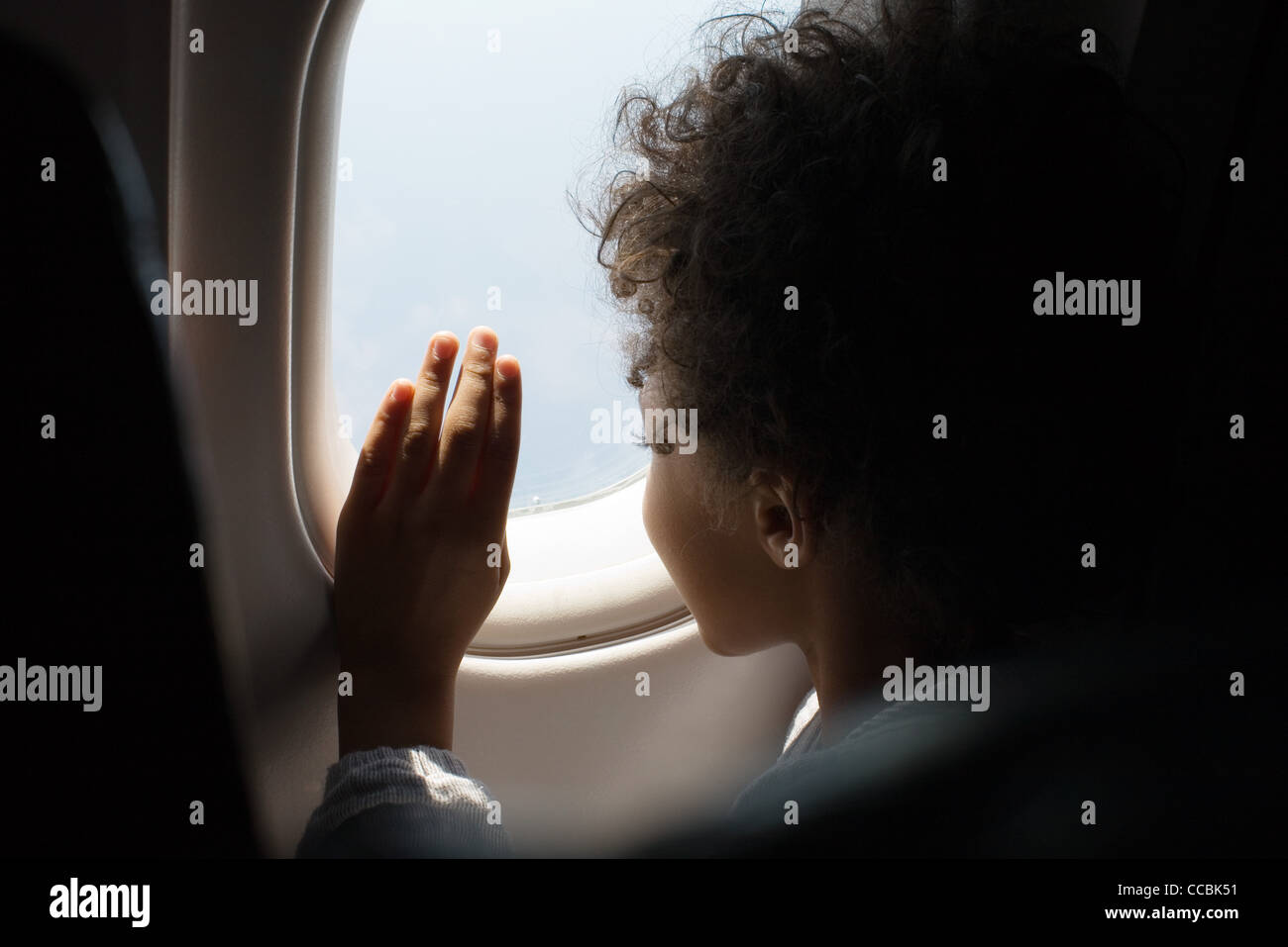 Boy looking out airplane window Stock Photo
