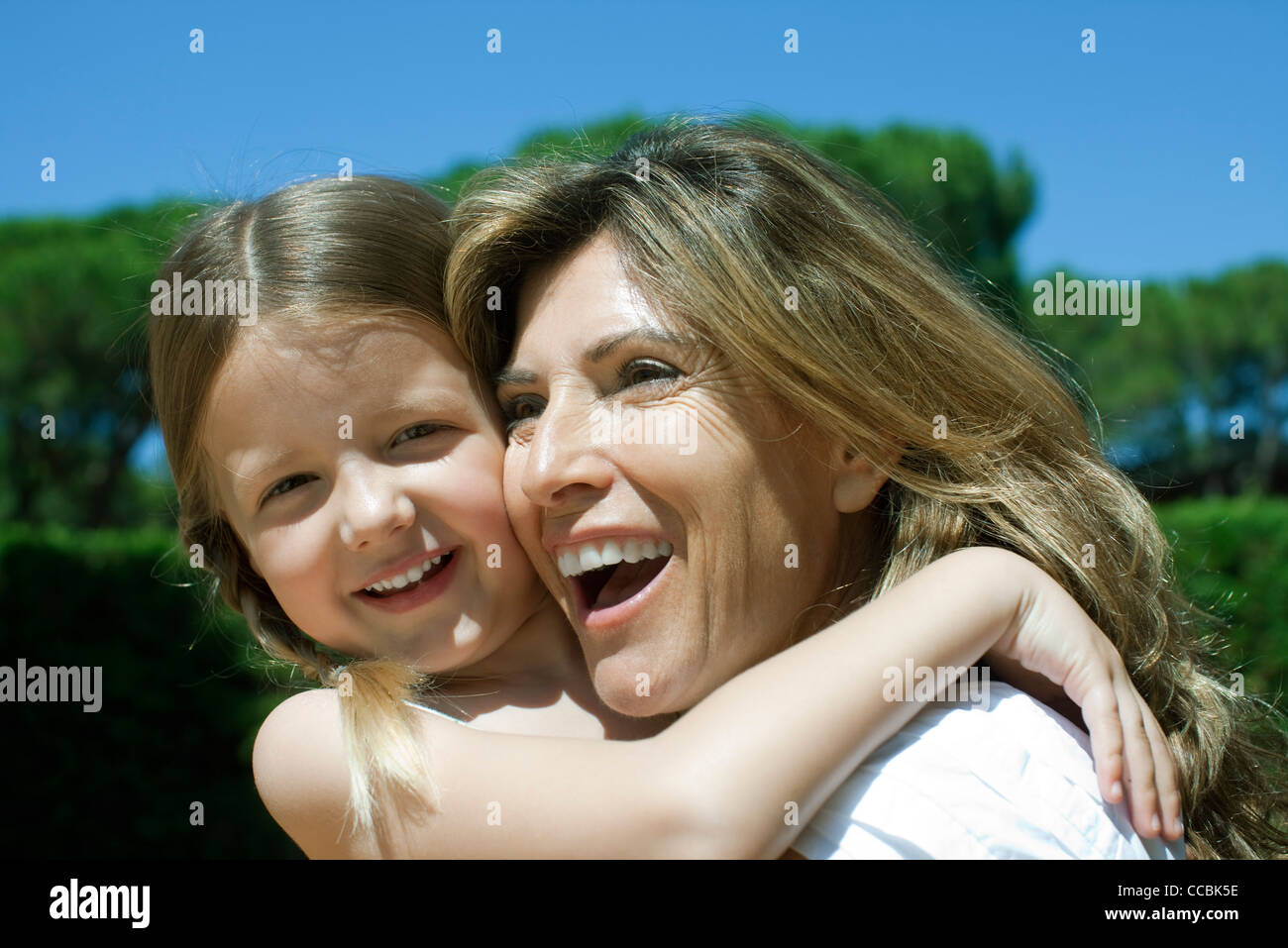 Happy mother and daughter embracing - Stock Image