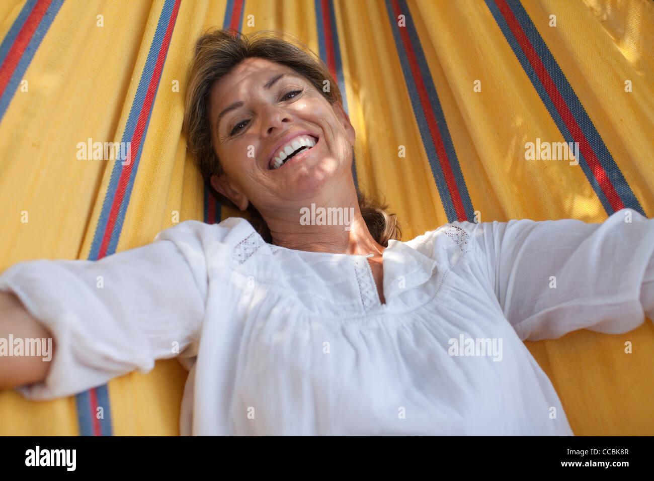 Woman relaxing in hammock, portrait - Stock Image