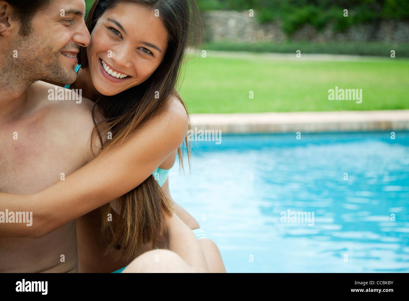 Couple embracing by swimming pool, portrait Stock Photo