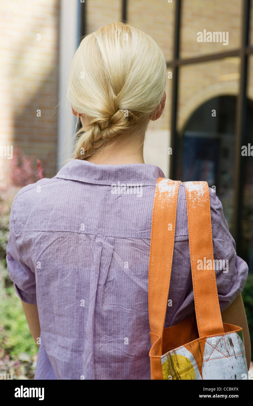 Young woman carrying shoulder bag, rear view - Stock Image