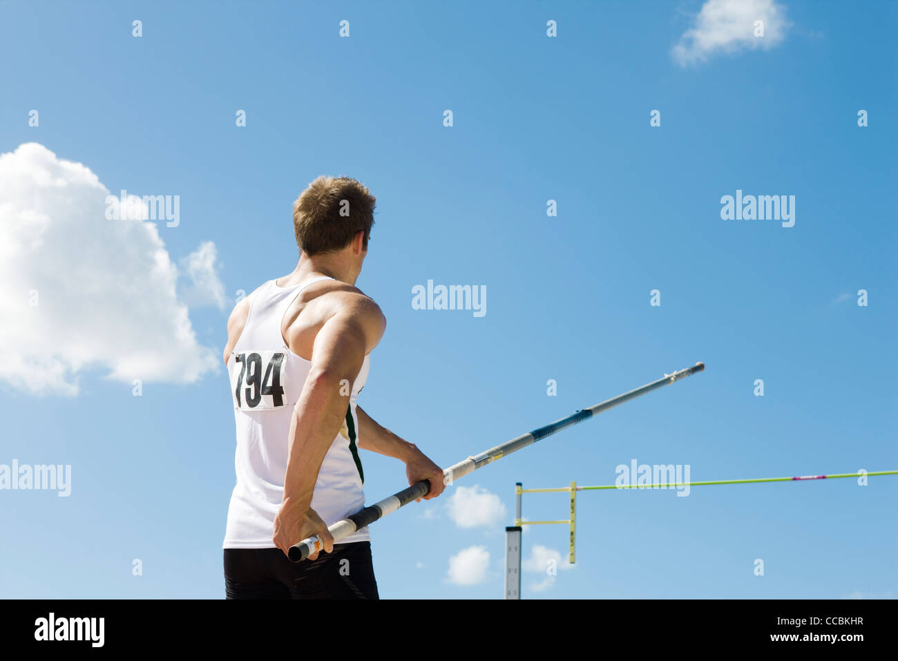 Athlete in pole vaulting competition, rear view - Stock Image