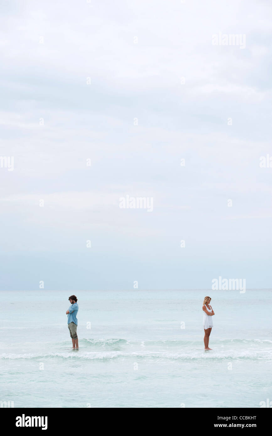 Couple standing apart in sea with backs turned toward each other - Stock Image