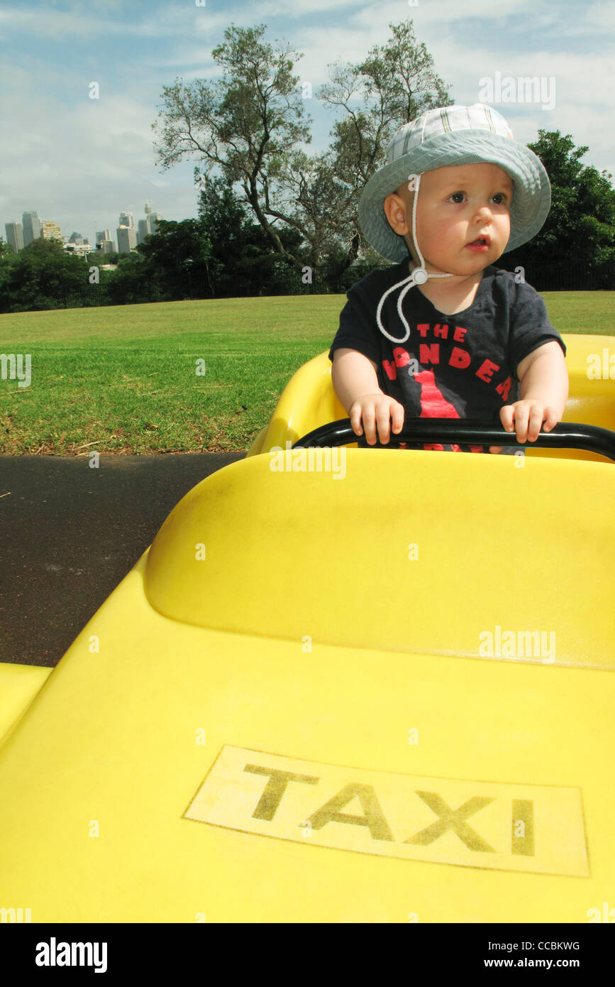 Baby riding in pretend taxi - Stock Image