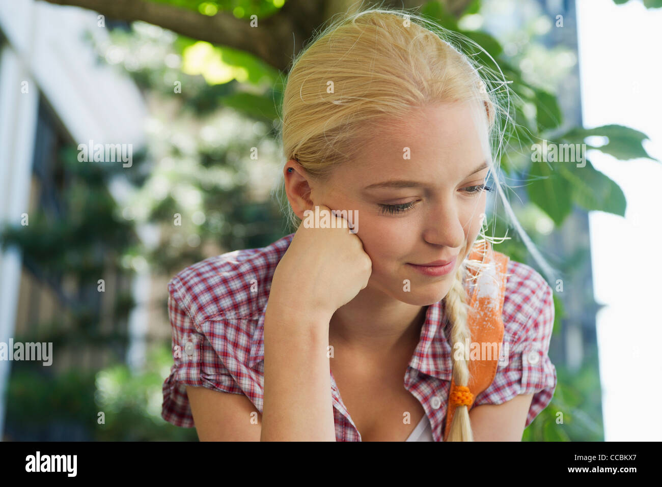 Young woman looking down in thought, portrait - Stock Image