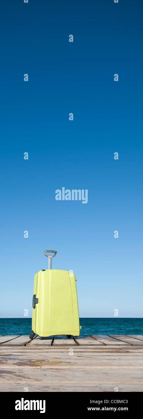 Yellow suitcase on pier - Stock Image