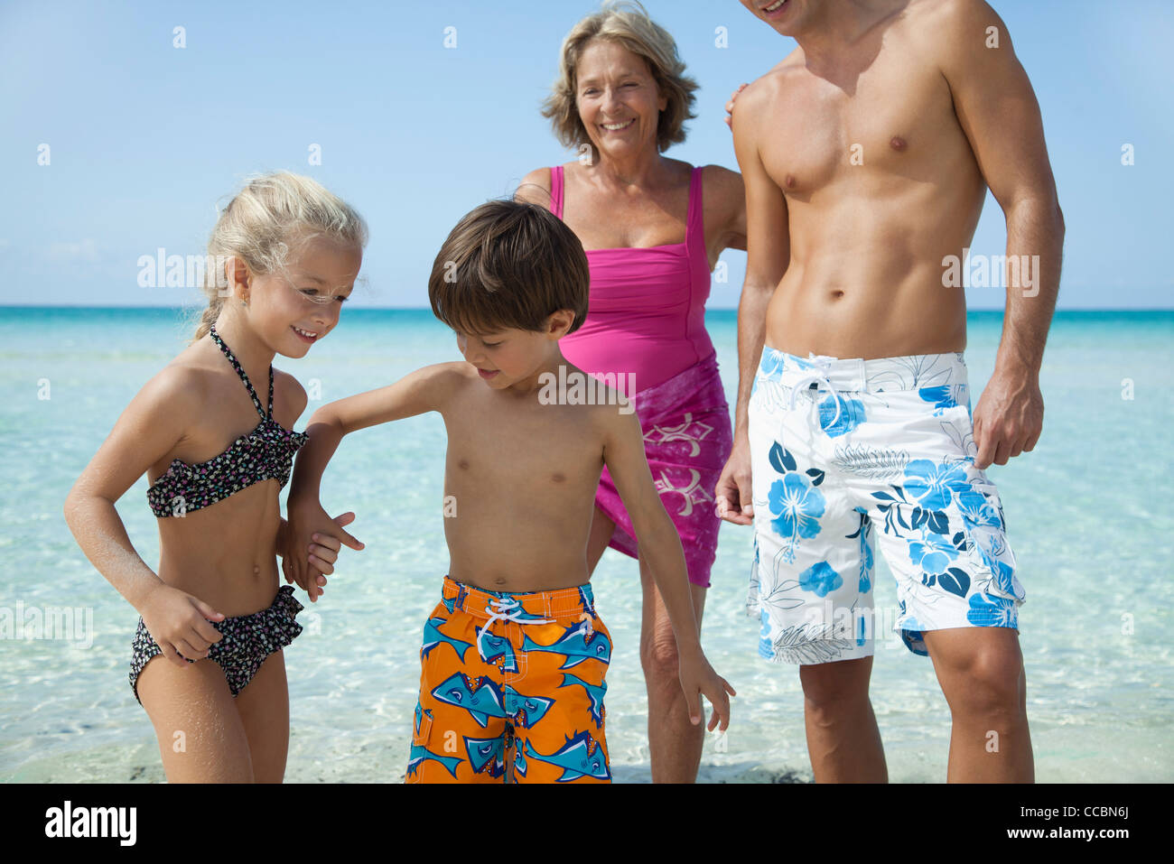 Children holding hands at the beach - Stock Image