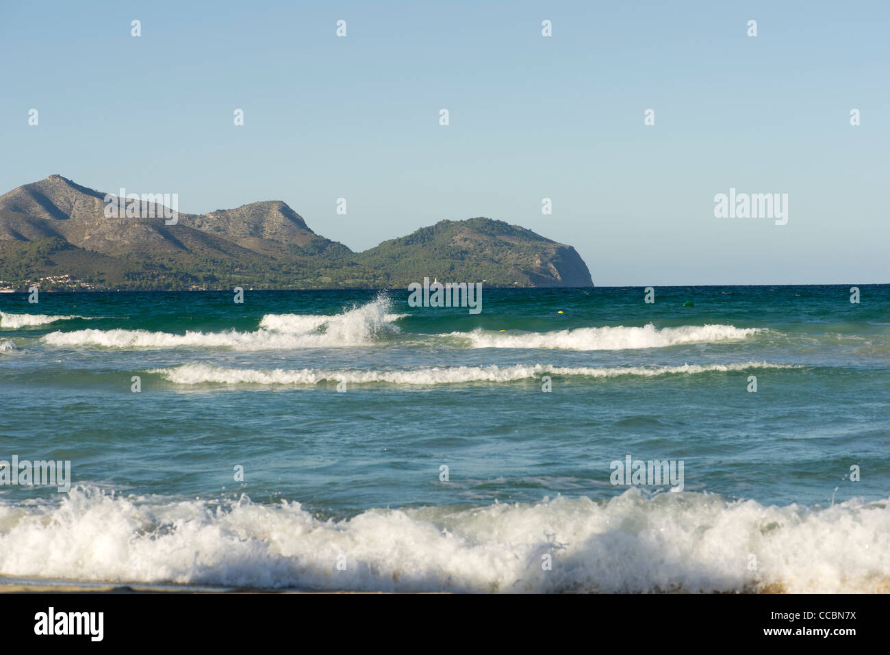 View of ocean, mountain in background - Stock Image