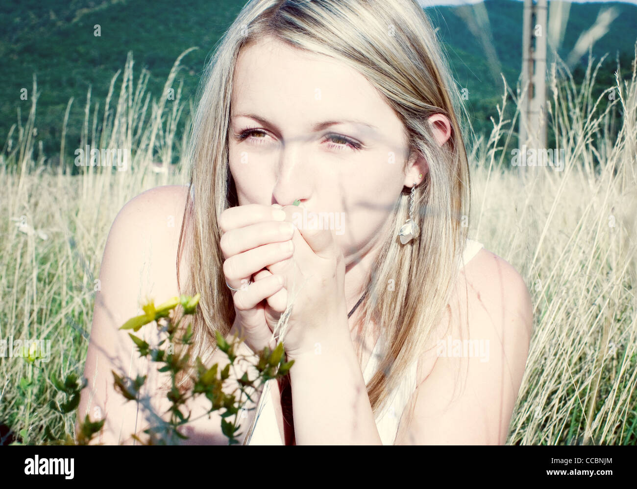 Woman blowing blade of grass Stock Photo