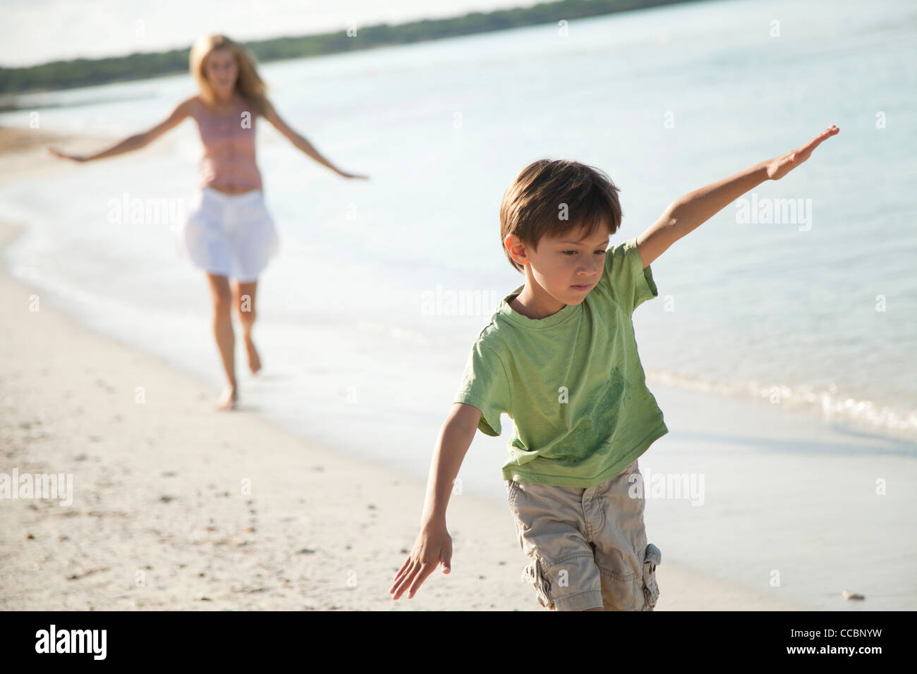 Boy running with arms out at the beach - Stock Image
