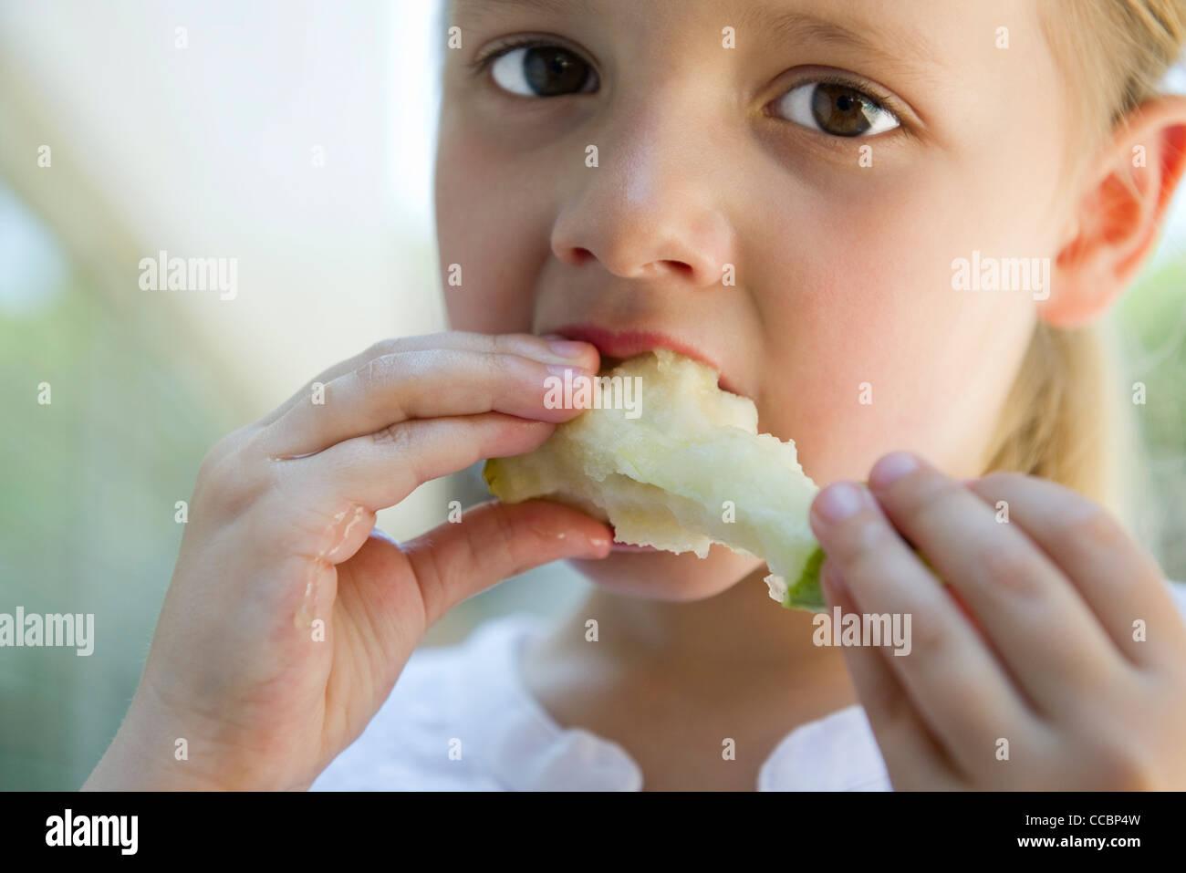 Little girl eatiing apple - Stock Image