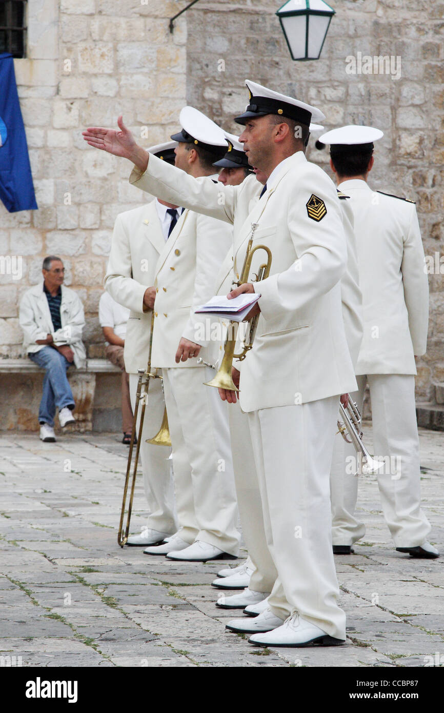 One band member gestures to another during St. Stephen's Day celebrations in Hvar, Croatia. - Stock Image