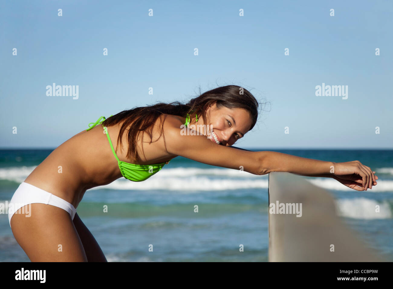 Woman in bikini stretching at the beach, portrait Stock Photo
