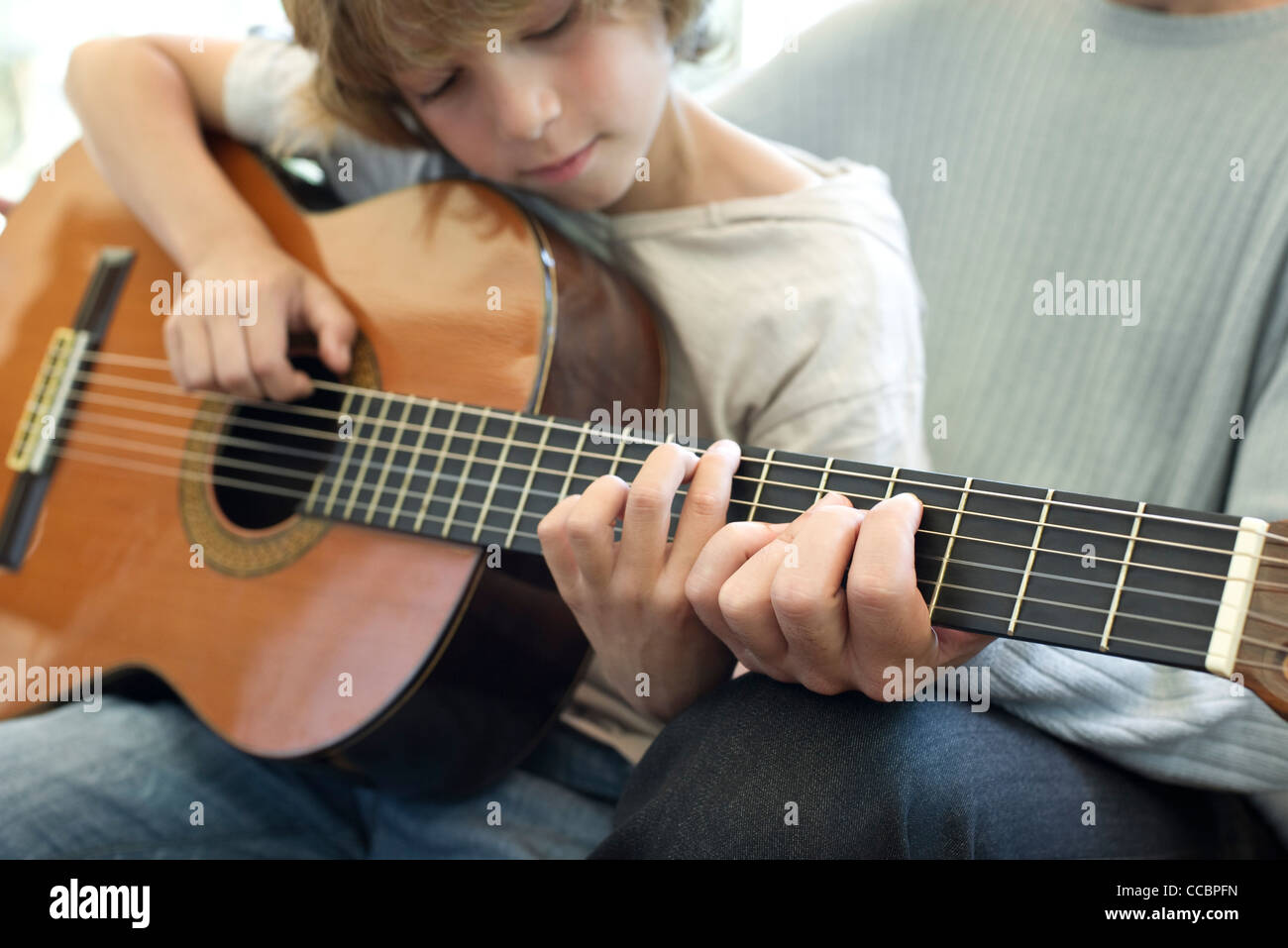 Boy learning how to play guitar with father Stock Photo