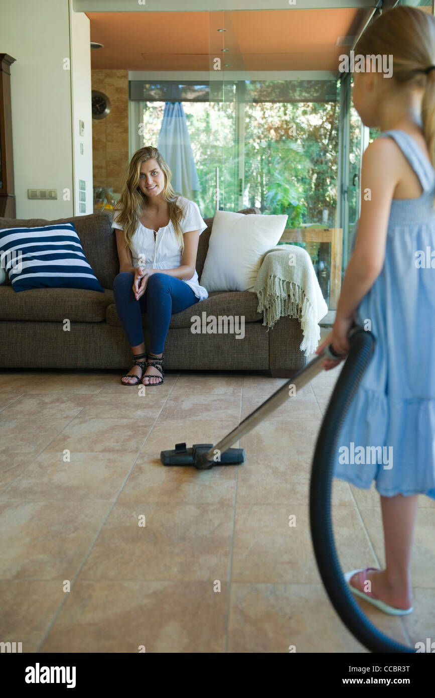 Woman sitting on sofa smiling, daughter vacuuming floor in foreground - Stock Image