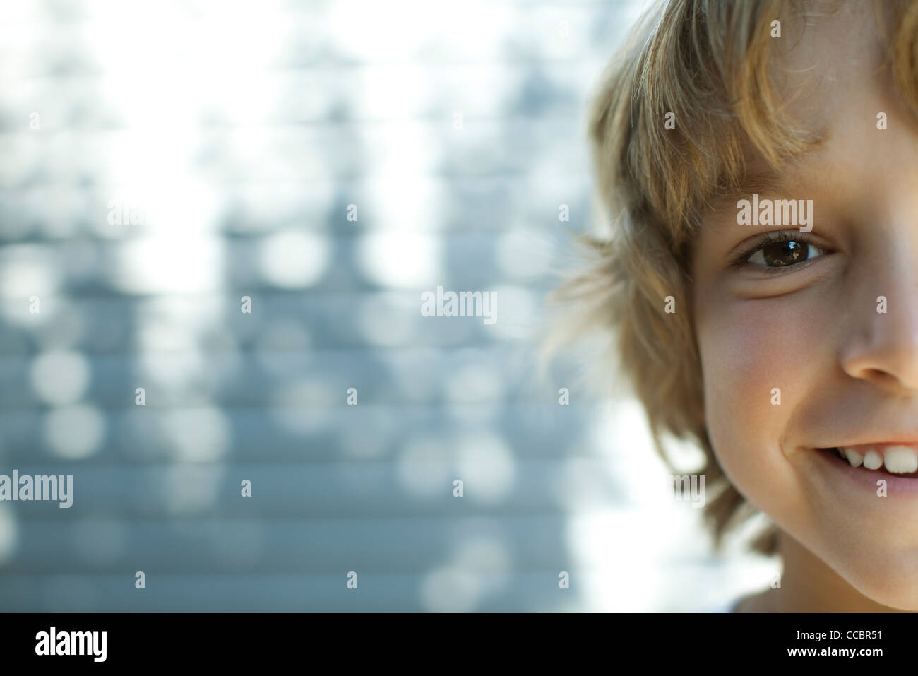 Boy smiling at camera, cropped portrait - Stock Image