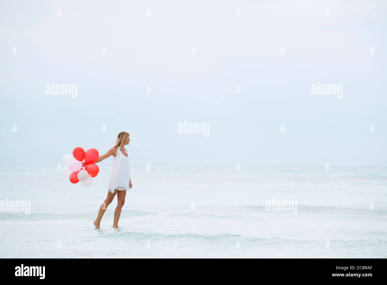 Woman walking on water, carrying bunch of balloons - Stock Image
