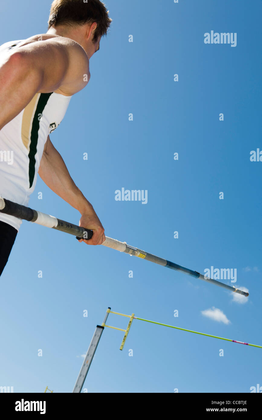 Athlete preparing for pole vault, low angle view - Stock Image
