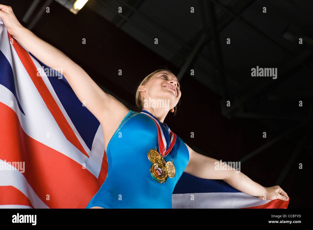 Female gymnastic medalist holding American flag, portrait - Stock Image