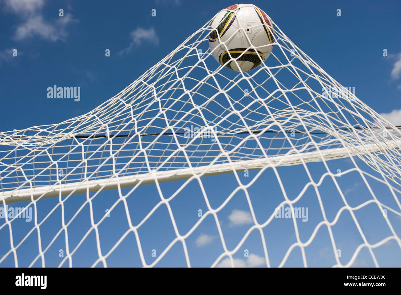 Soccer ball hitting net - Stock Image