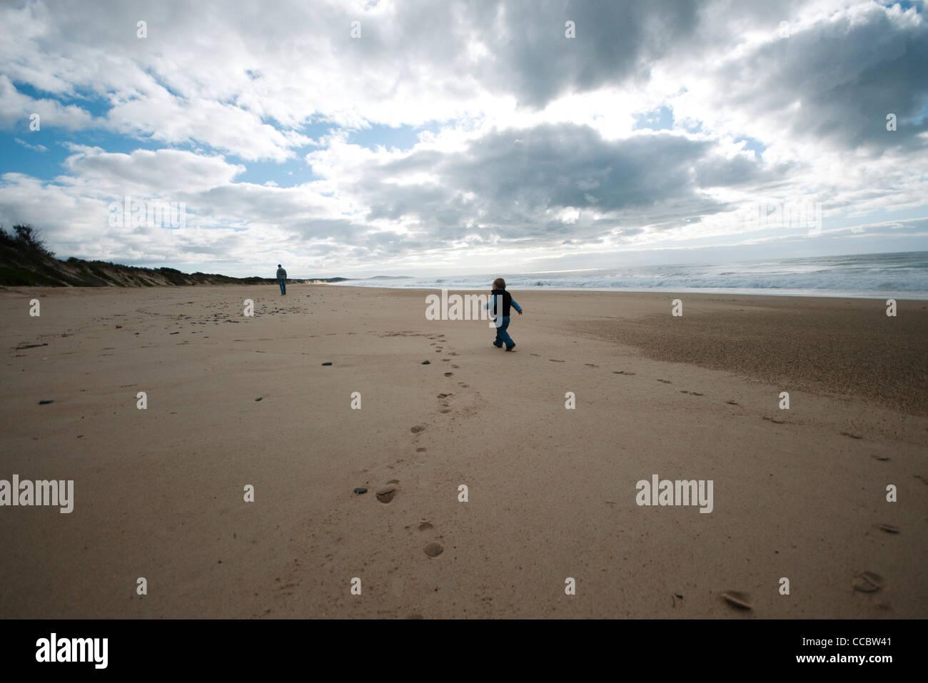 Toddler walking on beach - Stock Image