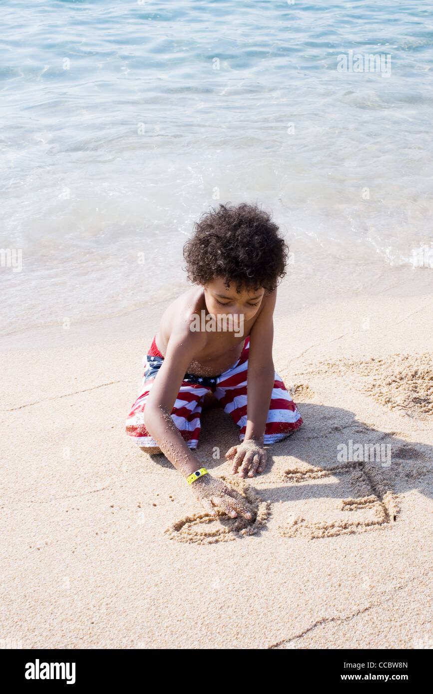 Boy writing in sand at the beach - Stock Image